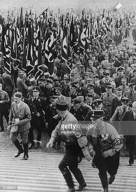 Nazi leader Adolf Hitler closely followed by officers including Rudolf Hess ascending steps to address a rally at Nuremberg