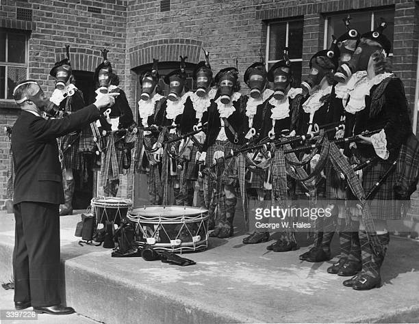 The Dagenham girl pipers practising their gas mask drill which makes playing their bagpipes difficult