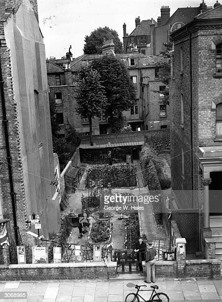When Mr Sabcha's house in Kensington, London was bombed he converted the site into an allotment to grow food. Visitors have to buy a Savings stamp...
