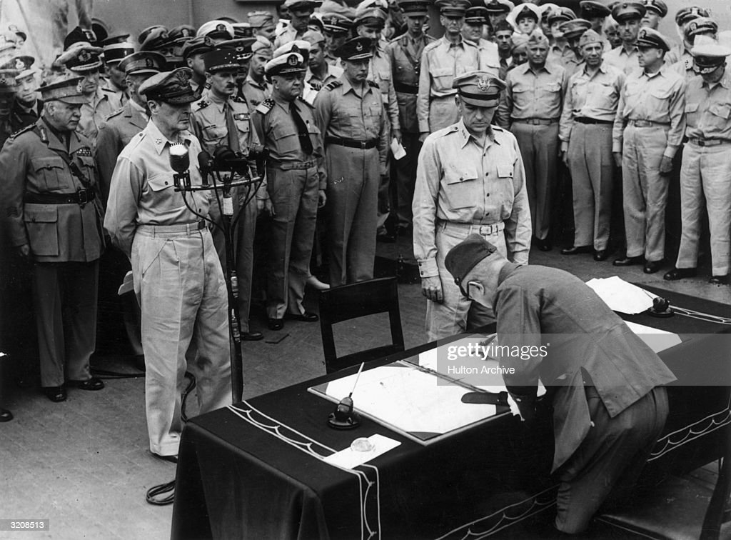 Japanese Imperial Headquarters representative General Yoshijiro Umezu (foreground; R) signing a surrender document while General MacArthur (foreground; C) watches, aboard the U.S.S. 'Missouri,' Tokyo Bay.