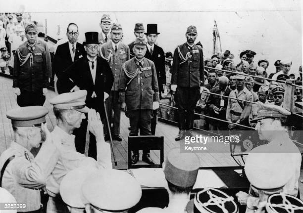 Sir Arthur Percival and Jonathan Wainwright salute General Douglas MacArthur as Supreme Commander of the Allied Forces just before he accepts the...