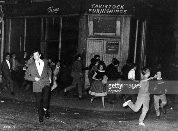 Teddy boys and girls run through Blenheim Crescent Notting Hill during the race riots in west London
