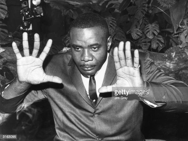 American World Heavyweight Boxing Champion Sonny Liston demonstrates the size of his huge hands at Mayfair Hotel in London