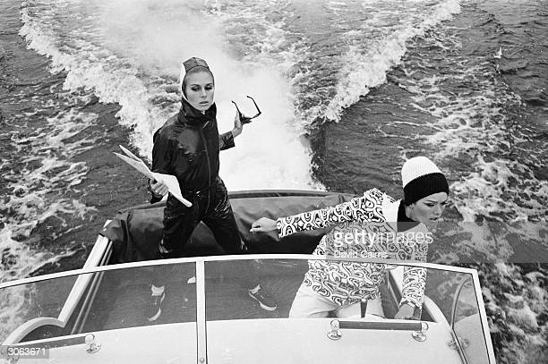Two models including Joanna Lumley left wearing a waterproof suit and a patterned sweater on a motorboat during a fashion shoot on the Thames