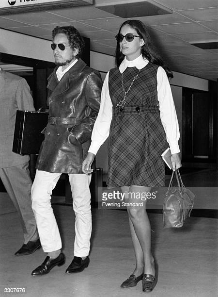 American electric folk hero Bob Dylan arriving at an airport with his wife Sara