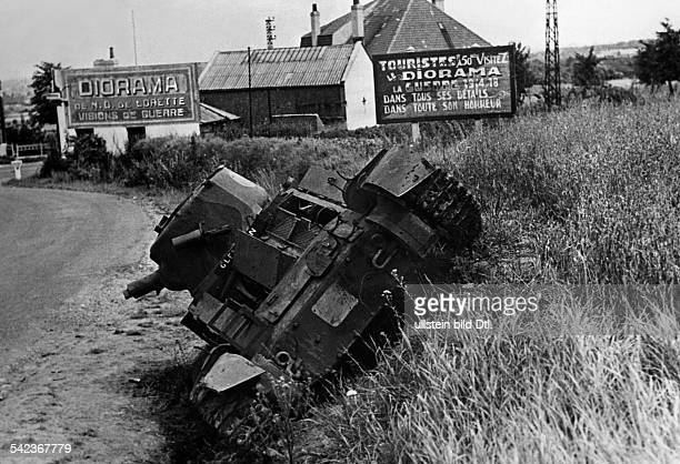 2wwcampaign in the west 1005 A wrecked british tank on the roadside Panels advertizing for a visit to historical WWI dioramas nearby June 1940...
