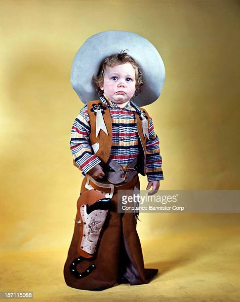 A 2yearold boy wearing a cowboy hat vest and chaps with a toy gun and holster 6th August 1947