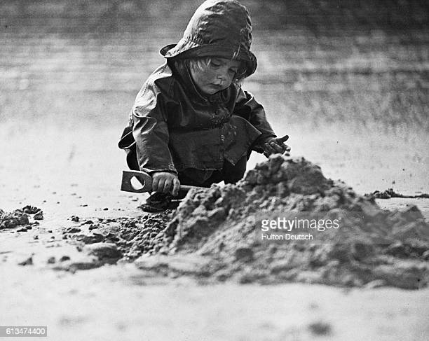 A 2yearold girl is undeterred by the rain as she plays on a beach in Kent