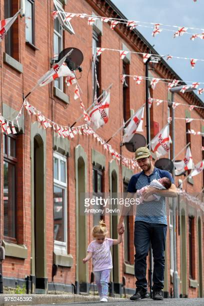 2yearold Lottie Rose Kenway holds hands with Stephen Mullane as he carries his 8weekold daughter Hollie Mullane on Wales Street in Oldham which local...