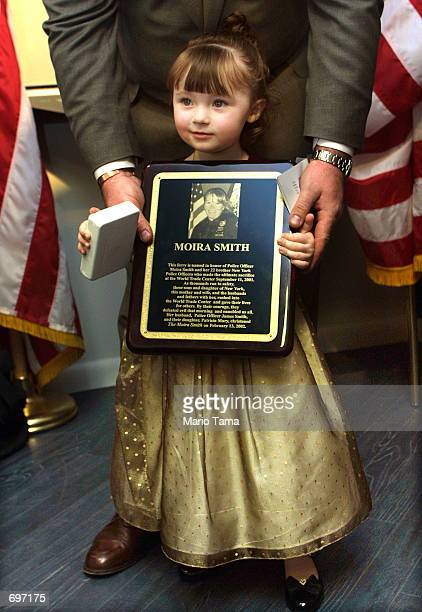 Year-old Patricia Mary Smith holds a plaque honoring her deceased mother, New York City Police Officer Moira Smith February 13, 2002 in New York...