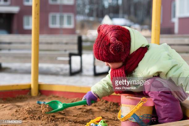 2-years-old little girl playing in the sandbox in a cold sunny winter day. - 2 girls 1 sandbox stock photos and pictures