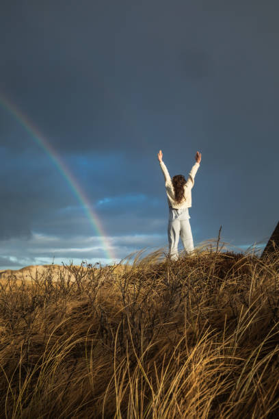 30s Woman Reaching to Sky With Rainbow In the Distance