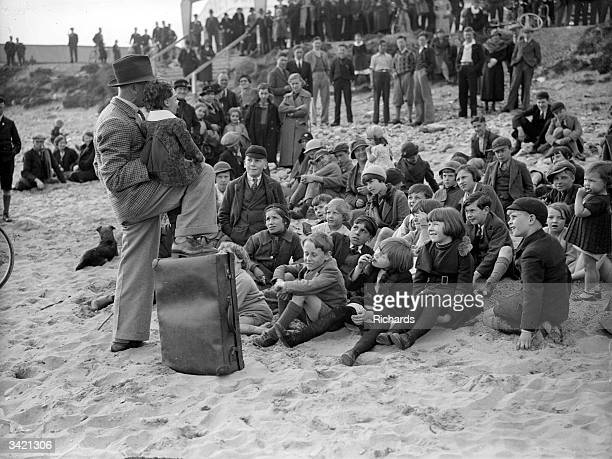 A crowd of holidaymakers on the beach at Porthcawl Mid Glamorgan Wales watching a performance by a ventriloquist and his doll