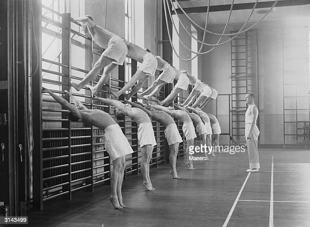 Mr Wilson the physical training instructor looks on while a group of trainee instructors exercise on the bars at the Carnegie Physical Training...