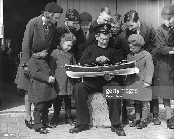 An old lifeboat man shows some schoolchildren a model of a lifeboat at the Royal National Lifeboat Institution museum in Eastbourne