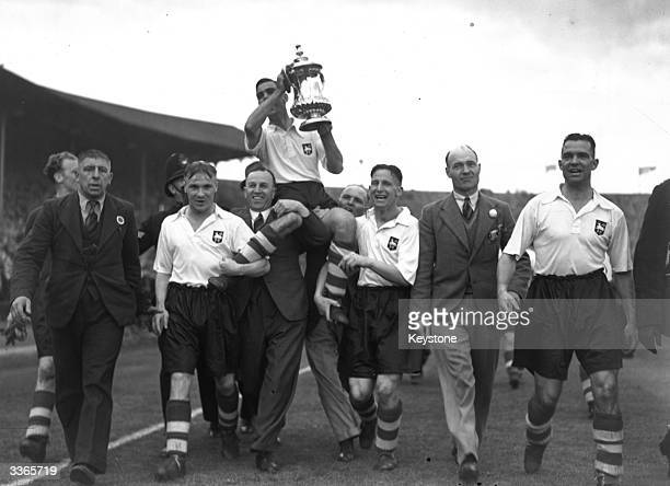 Preston North End carry the FA Cup trophy on a victory lap of honour after beating Huddersfield Town 1-0 in the FA Cup Final at Wembley.