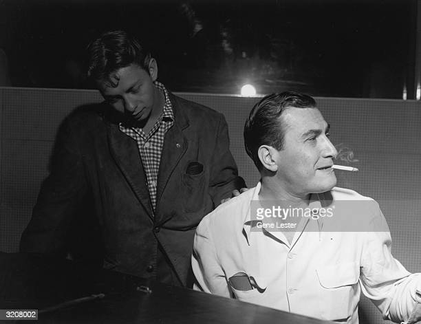 EXCLUSIVE American bandleader and musician Artie Shaw smokes a cigarette between his teeth in front of a piano while vocalist Mel Torme stands behind...