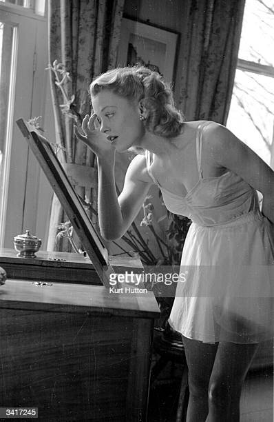A woman in tailored vest and panties by Petalena checks her makeup in a mirror Original Publication Picture Post 4758 Nylon For Lingerie pub 1949