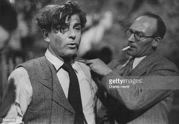 Welsh film director and actor Emlyn Williams left being helped on with his jacket after a fight scene in his film 'The Last Days Of Dolwyn' Original...
