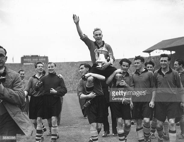 Wolverhampton Wanderers captain Billy Wright and the FA Cup trophy are held aloft by the Wolves team after their 31 victory over Leicester City in...