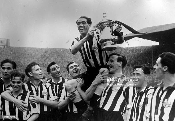 Newcastle United Football Club captain Joe Harvey is held aloft with the FA Cup trophy after their 20 victory over Blackpool in the FA Cup final at...