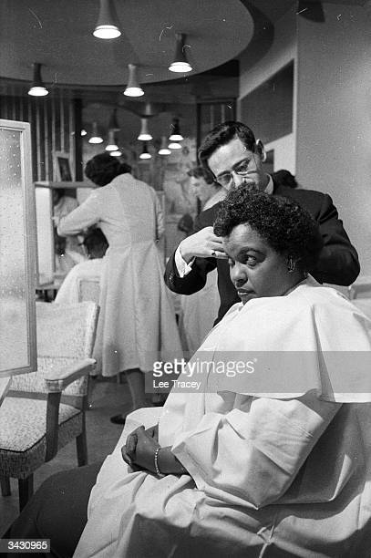 Trinidadian pianist Winifred Atwell has her hair straightened out at her own hairdressing salon in Brixton London