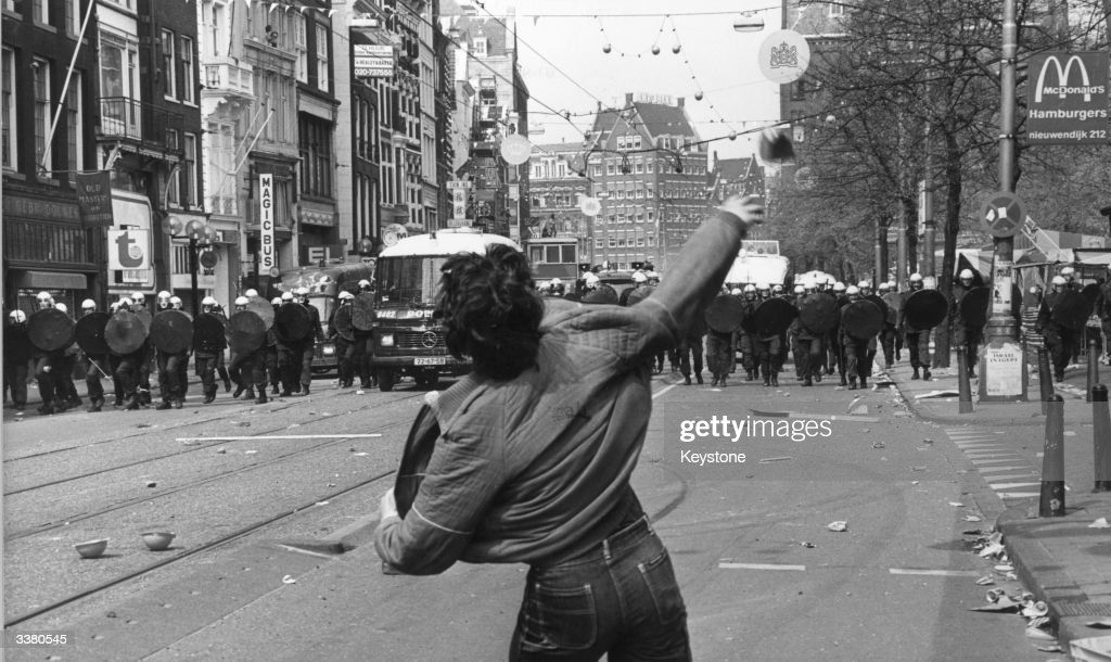 A Lone Protester Defiantly Throwing A Brick Towards A Line Of