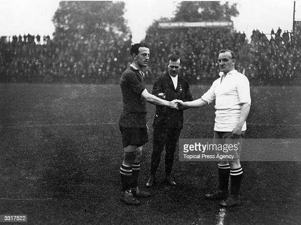 Captains Mavin of Fulham and Cameron of Bury shake hands before the start of the match with the referee looking on
