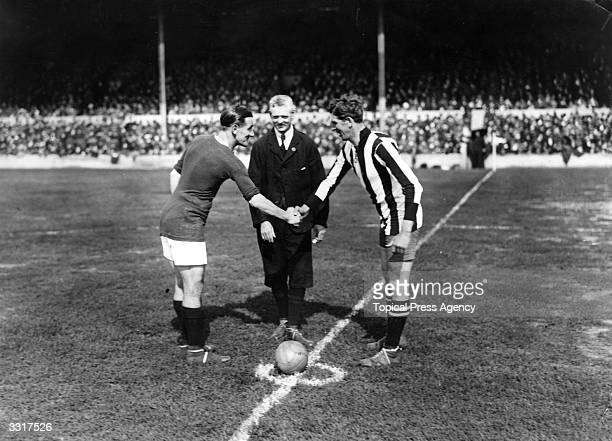 The captains of Woolwich Arsenal and Newcastle United shake hands before the start of the opening match of the season