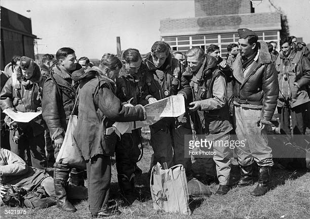 Pilots checking their maps before flying to Berlin on a bombing raid.