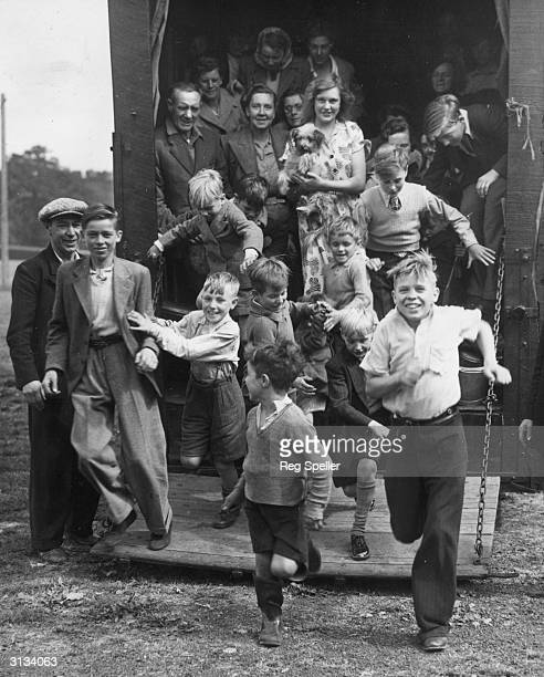 A crowd of London hop pickers burst through the open door of a truck on arrival at Buston Manor Farm in Maidstone Kent