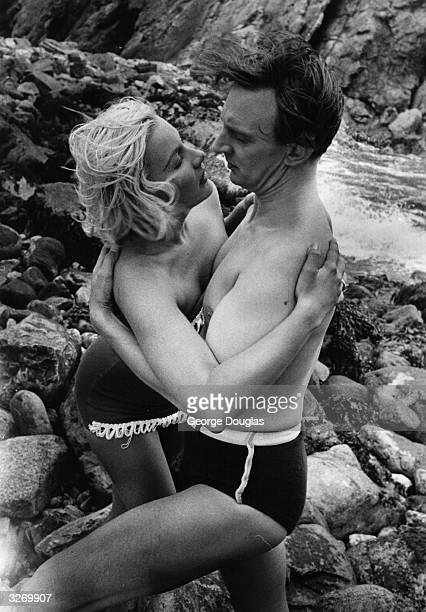 American actress Barbara Payton with Stephen Murray on the beach during the filming of 'The Four Sided Triangle' with Terence Fisher directing...
