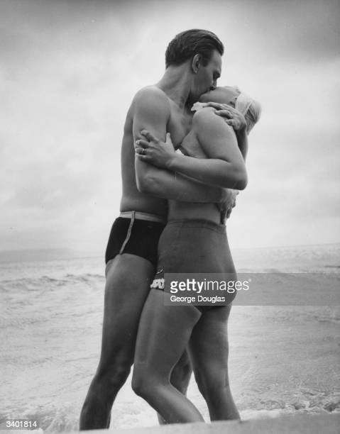 American film actress Barbara Payton in an embrace with her leading man Stephen Murray for a scene in the British film 'The Four Sided Triangle'...