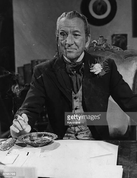 Sir Noel Pierce Coward English actor complete with monocle playing the role of 'Roland Hesketh Bascott' during the filming of 'Around the World in...