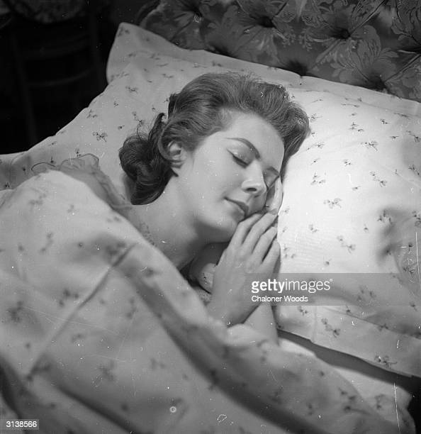 A serene looking woman falls asleep on a matching pillowcase and duvet cover from Harrods department store in London