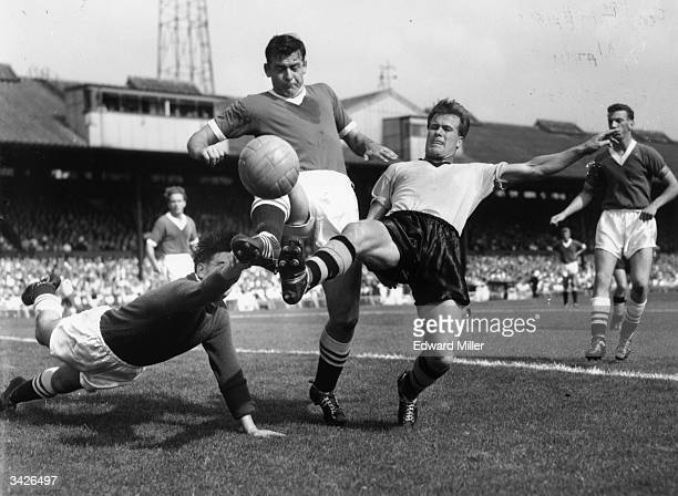 Wolverhampton Wanderers centre forward Jackie Henderson competes for the ball in the opposition goal area with Chelsea defender Peter Sillett and...
