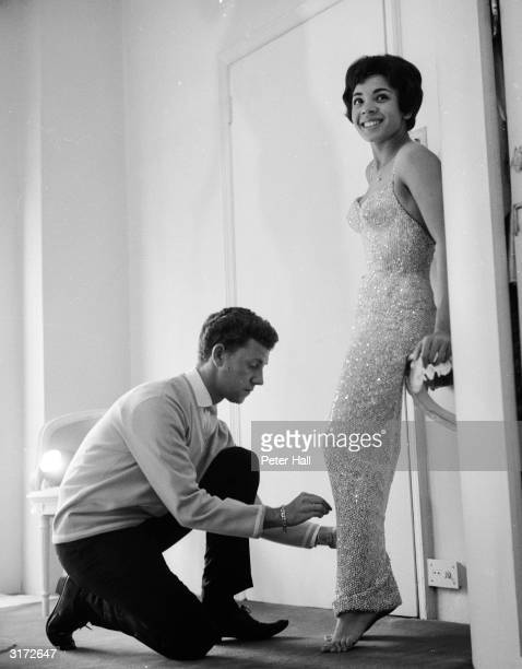 Welsh singer Shirley Bassey being fitted for a new dress by designer Douglas Darnell The sheath dress is covered with 156000 diamante stones and...