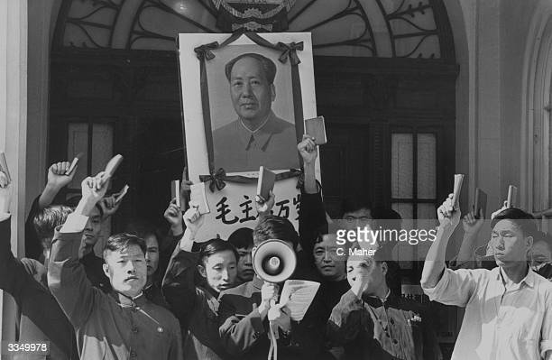 A Chinese delegation outside the London's Chinese Embassy holding a portrait of Mao Tse Tung and waving copies of his 'Little Red Book' in the air...