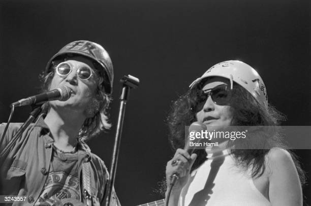British rock singer and songwriter John Lennon and his wife Japanese artist and singer Yoko Ono perform on stage wearing army helmets at the 'One to...
