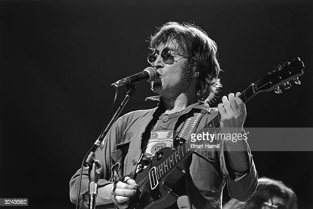 British rock singer and songwriter John Lennon sings and plays electric guitar on stage at the 'One to One' festival to benefit developmentally...