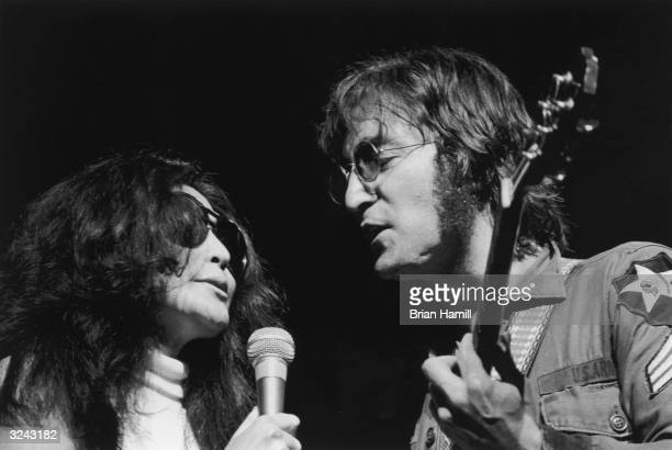 Headshot of Japanese artist Yoko Ono and her husband British rock singer and songwriter John Lennon singing on stage at the 'One to One' festival to...