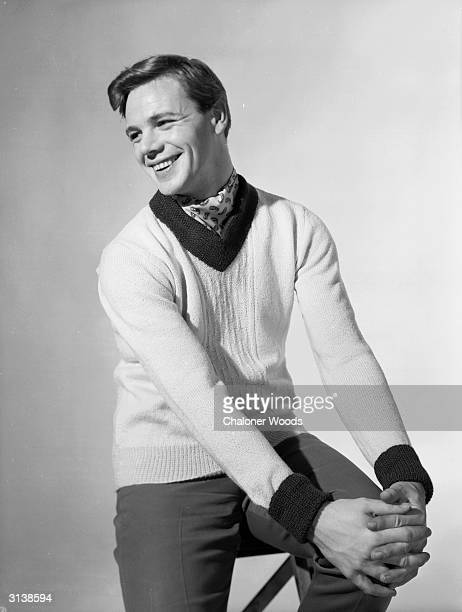 A 50s fashion model wearing a woollen Vneck pullover and casual slacks