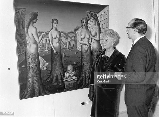 Peggy Guggenheim with Norman Reid the director of the Tate Gallery looking at the painting 'The Break of Day' by the Belgian surrealist Paul Delvaux...