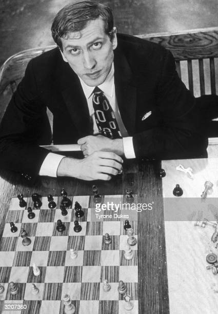 Highangle portrait of American chess champion Bobby Fischer looking up while sitting behind a chess board