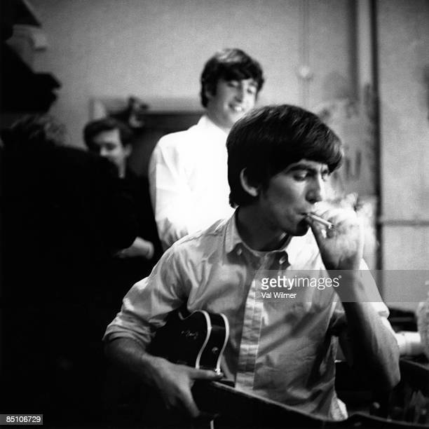 George Harrison from The Beatles smokes a cigarette backstage with John Lennon behind at the Finsbury Park Astoria London during the band's Christmas...