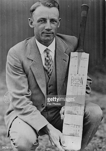 Australian batsman Don Bradman holding a personalized cricket bat