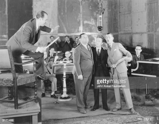 From left to right Oliver Hardy Stan Laurel and Charley Chase sing into an overhead microphone in a recording studio while the musicians follow a...
