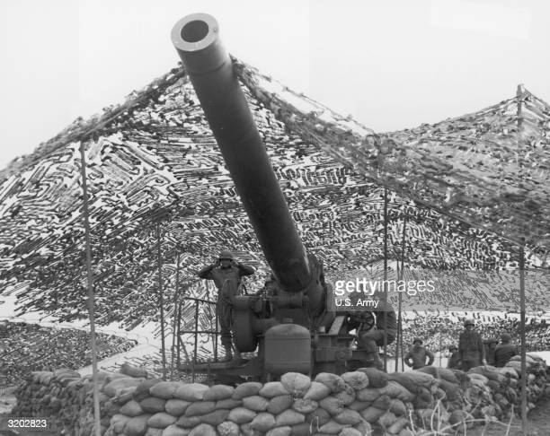 Soldiers, camouflaged under a tarp, hold their ears as they prepare to fire a missile from a 240mm Howitzer into German-held territory, Italy, World...