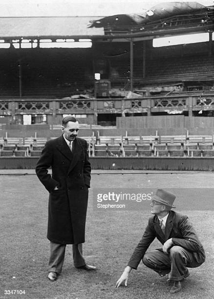 Colonel A D C Macauley, Secretary of the All England Tennis Club, Wimbledon, examines the turf on the centre court with head groundsman E J Fuller.