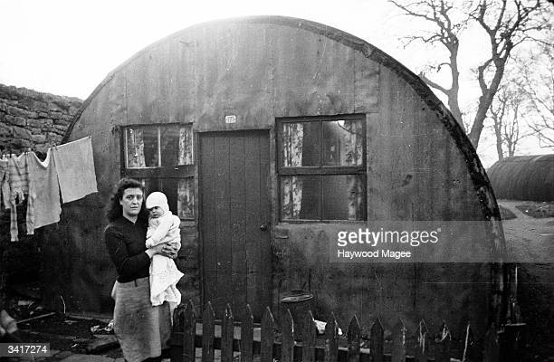 A mother holding her baby in front of a Nissen hut at Duddingston Camp in Edinburgh The basic tin shelters were built as temporary accommodation for...